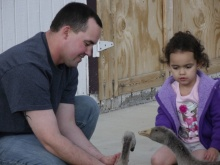 Veronica Brown and her father Dusten Brown play with geese at their home in Nowata, Oklahoma.